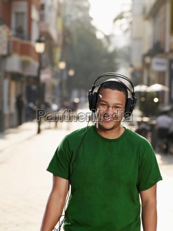 young man in street wearing headphones