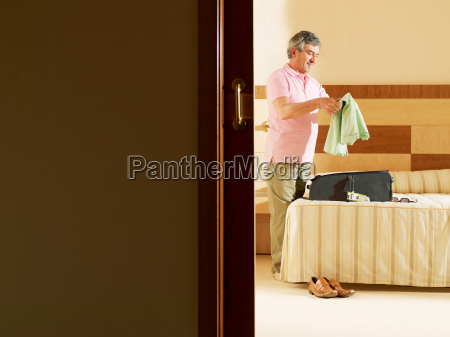 senior adult man unpacking clothes