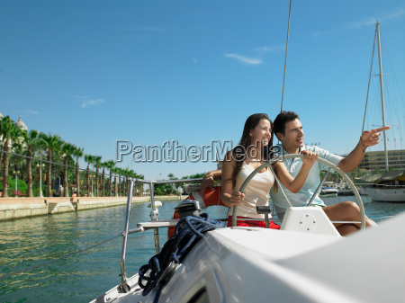young couple at wheel of yacht