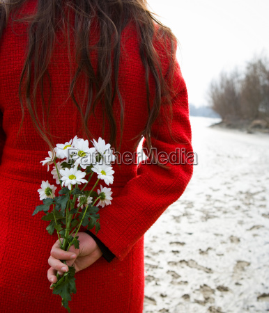 young woman holding flowers behind back