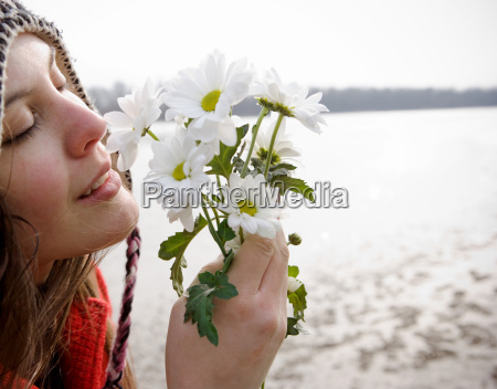 young woman holding flowers to nose