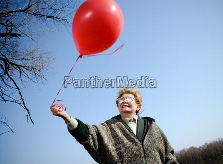 senior woman holding red balloon