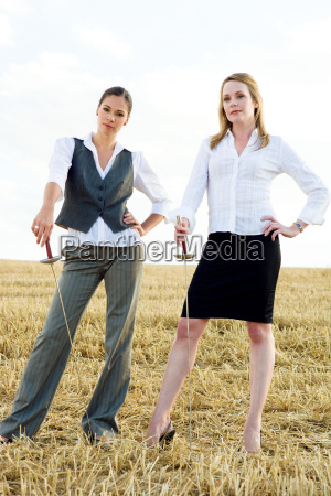two women standing with swords