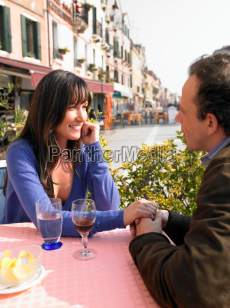 couple holding hands at restaurant