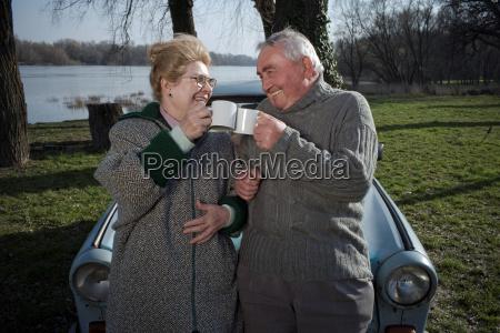senior couple by car toasting each