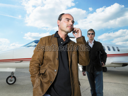 two men beside private jet