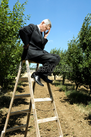 man sitting on ladder holding his