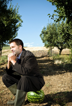 man sitting on watermelon in orchard