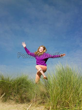 teenage girl jumping through grass