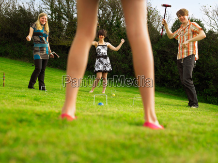 man and women playing croquet in