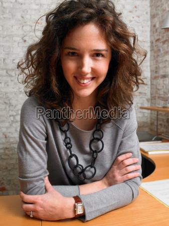 woman sitting at desk smiling at