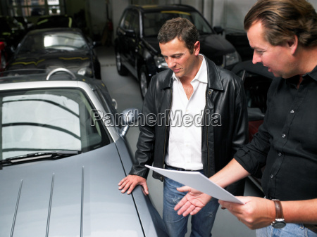 two men in a garage discussing