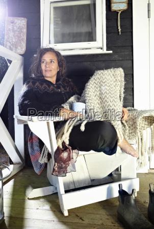 woman relaxing in armchair indoors