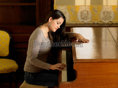 young woman playing piano with one