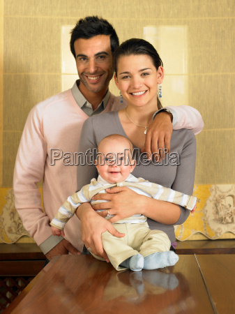 young couple and baby son smiling