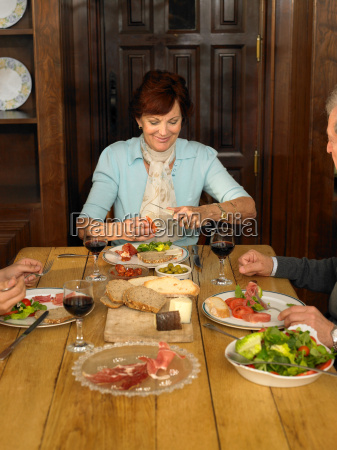 senior woman having lunch with family