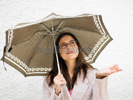 woman holding umbrella holding out hand