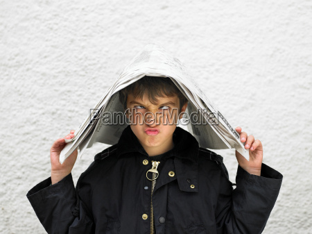 boy covering head with newspaper