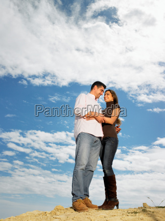 couple embracing on hilltop