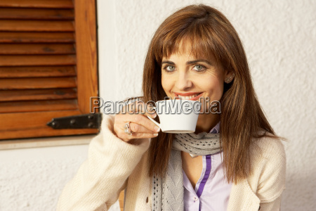 woman drinking from cup smiling