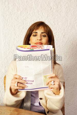 woman sitting at table reading magazine