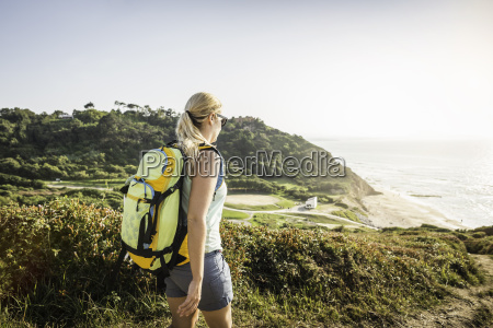 young woman hiking on coastal path