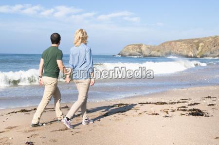 mid adult couple walking on beach