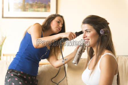 young woman doing friends hair