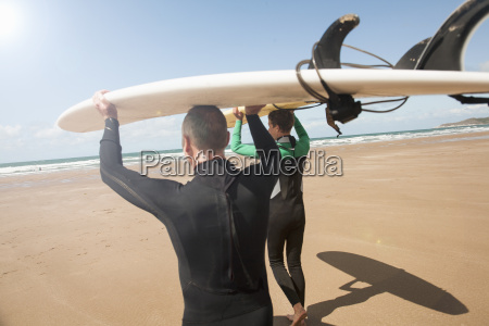 man and teenage boy carrying surfboards