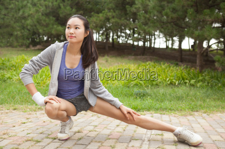 young female runner stretching legs in