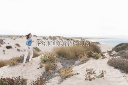 mid adult woman running up sand