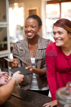two female friends paying bill in