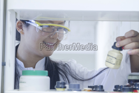 female scientist selecting chemical from shelf