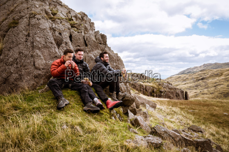 three young male hiking friends eating