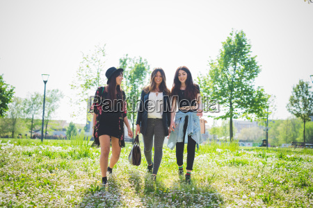 three young female friends strolling in