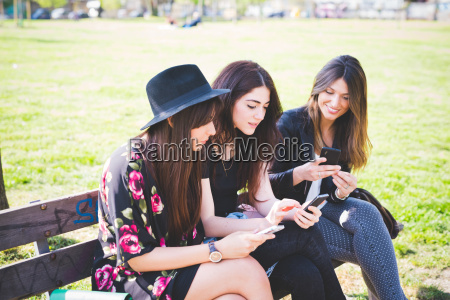 three young female friends reading their