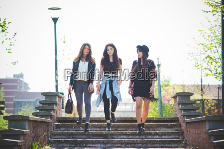 three young female friends strolling down