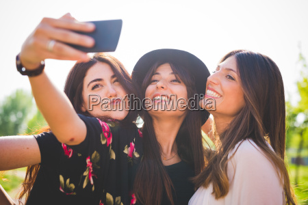 three young female friends taking smartphone