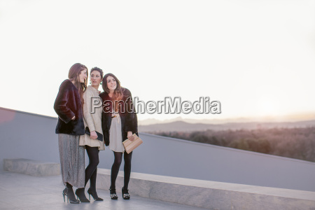three female friends standing together at