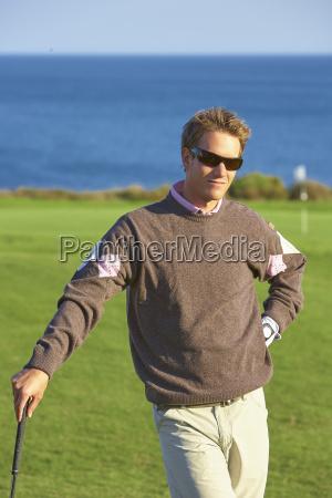 golfer wearing sunglasses leaning against golf