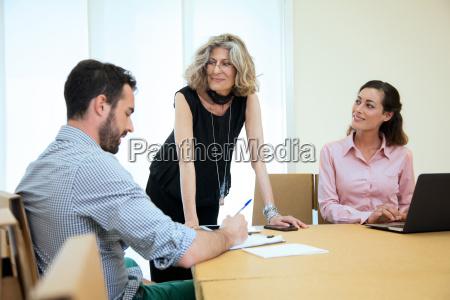 three designers brainstorming at boardroom table