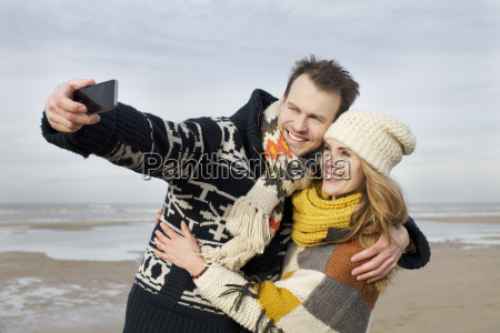mid adult couple taking selfie with