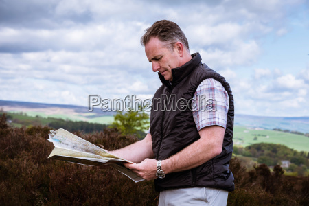 male hiker reading map on heather
