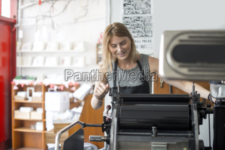young woman working on traditional letterpress