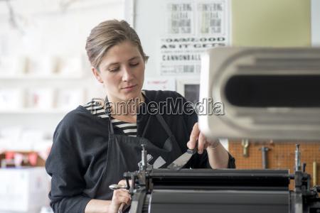 female letterpress printer inking machine in