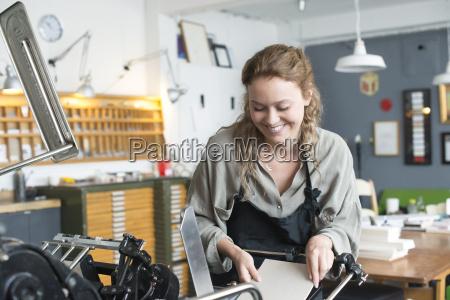female printer inserting paper to print