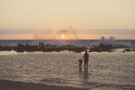 silhouetted mother and female toddler paddling