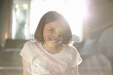sunlit illuminated portrait of smiling girl