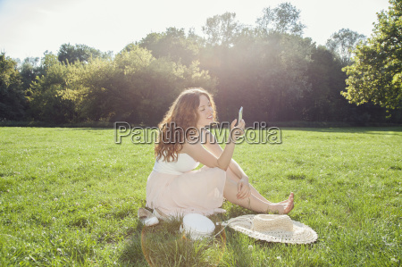 young woman sitting on park grass