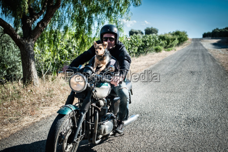 mature man and dog riding motorcycle